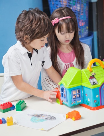 Little boy and girl playing with plastic house at desk in kindergarten
